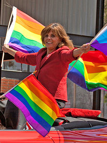 Jane Velez-Mitchell waving pride flags from a car